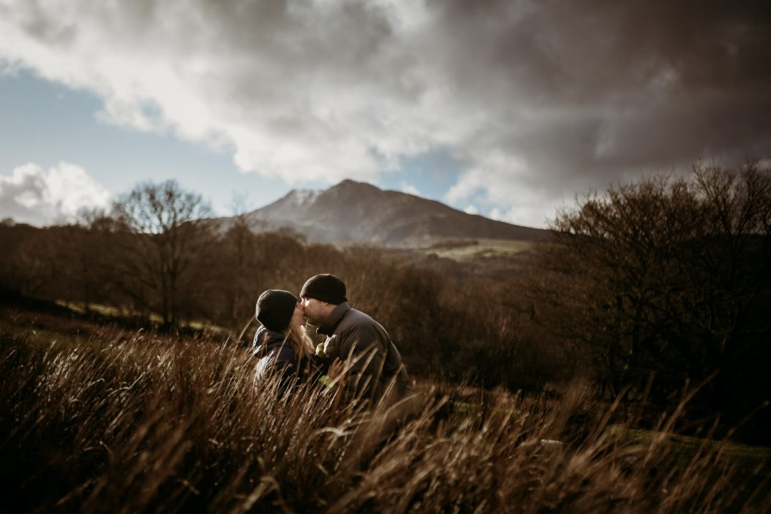 couple kissing in high grass in front of a snow capped hill in Snowdonia