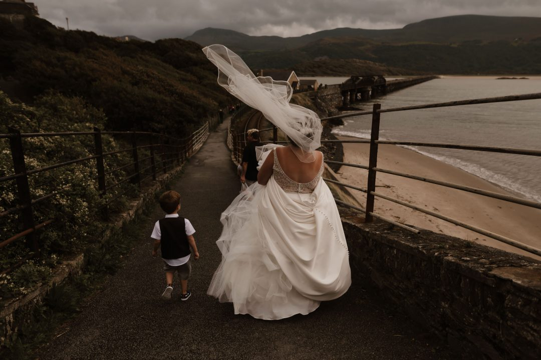 bride and her son walking towards Barmouth bridge with her veil blowing in the wind by North Wales Wedding Photographer
