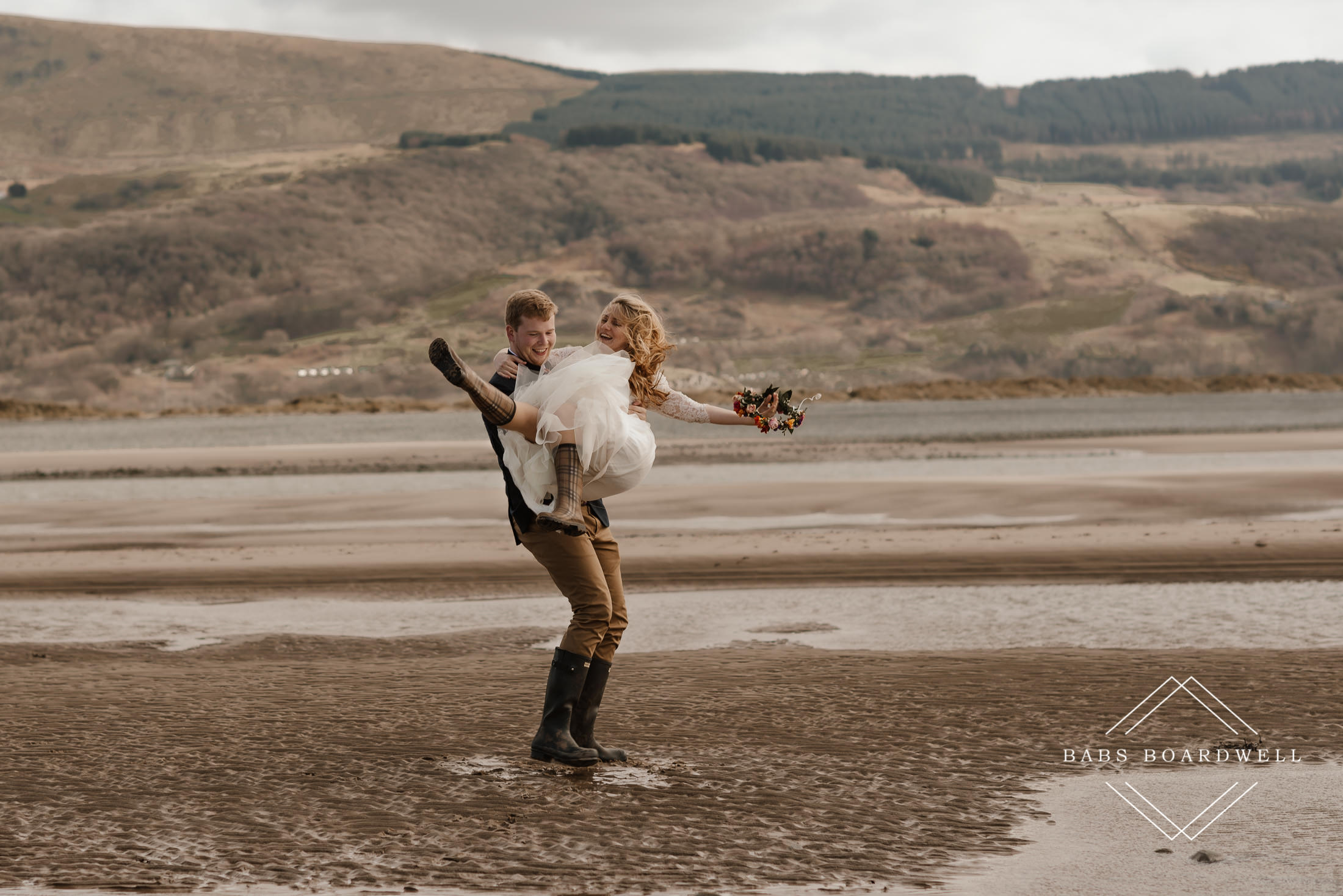groom holding bride wearing a flower crown and Wellington boots twirling on Barmouth Beach by North Wales Wedding Photographer