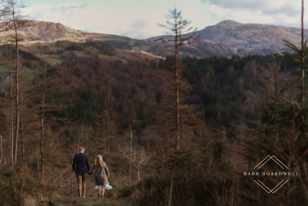 bride and groom walking on a path overlooking Cadair Idris on their Elopement Wedding day by North Wales Wedding Photographer