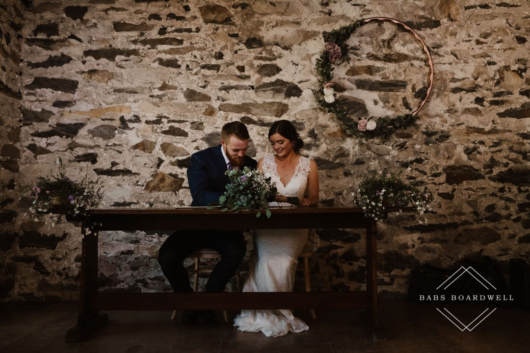 bride and groom signing the registry at Llyn Gwynant Wedding Barns by Snowdonia Wedding Photographer