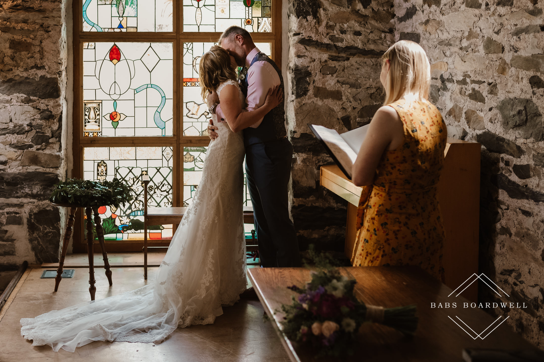 bride and groom sharing their first kiss as husband and wife overlooked by registrar and shot by Snowdonia Wedding Photographer