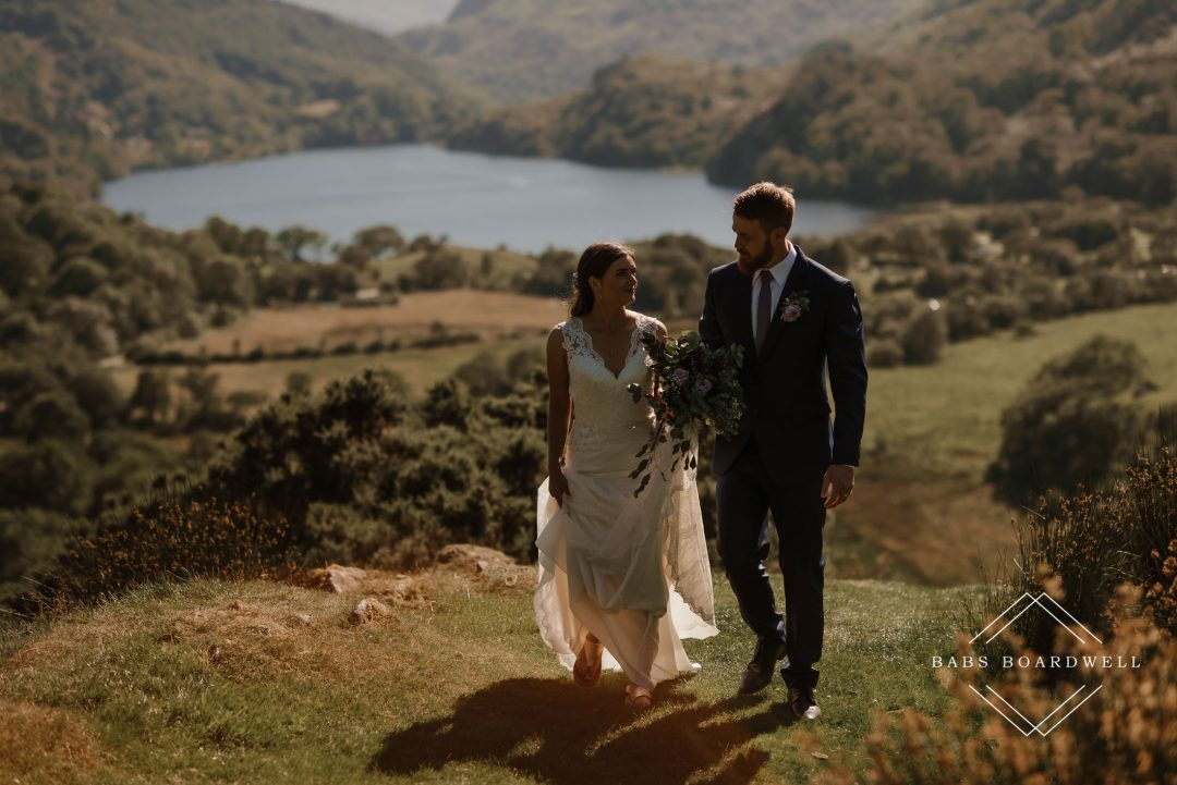 bride and groom walking towards Snowdonia Wedding Photographer with Llyn Gwynant in the background