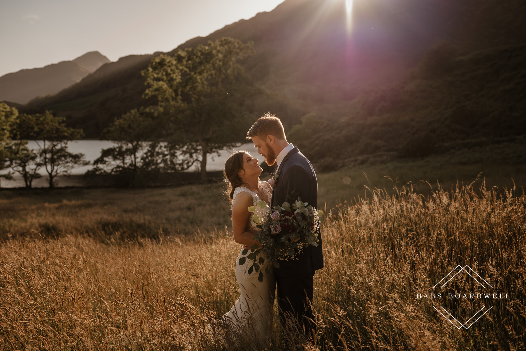 bride and groom hugging by Llyn Gwynant at sunset by Snowdonia Wedding Photographer