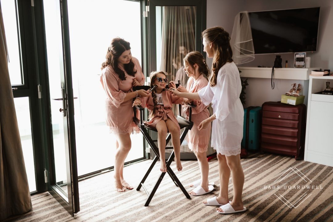 bride and bridesmaids getting ready standing around a flower girl on a high make-up chair with light streaming in from the back by North Wales Wedding Photographer