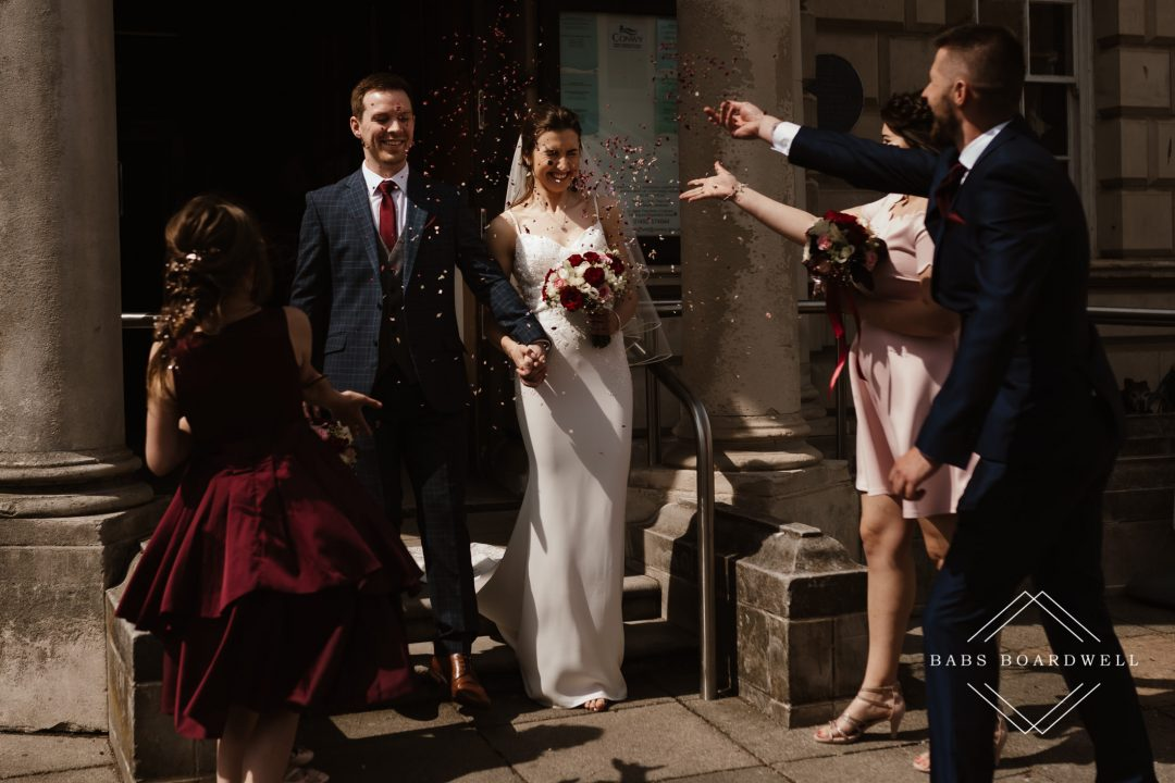 bride and groom leaving Llandudno Registry Office having confetti thrown over them by their guests by North Wales Wedding Photographer