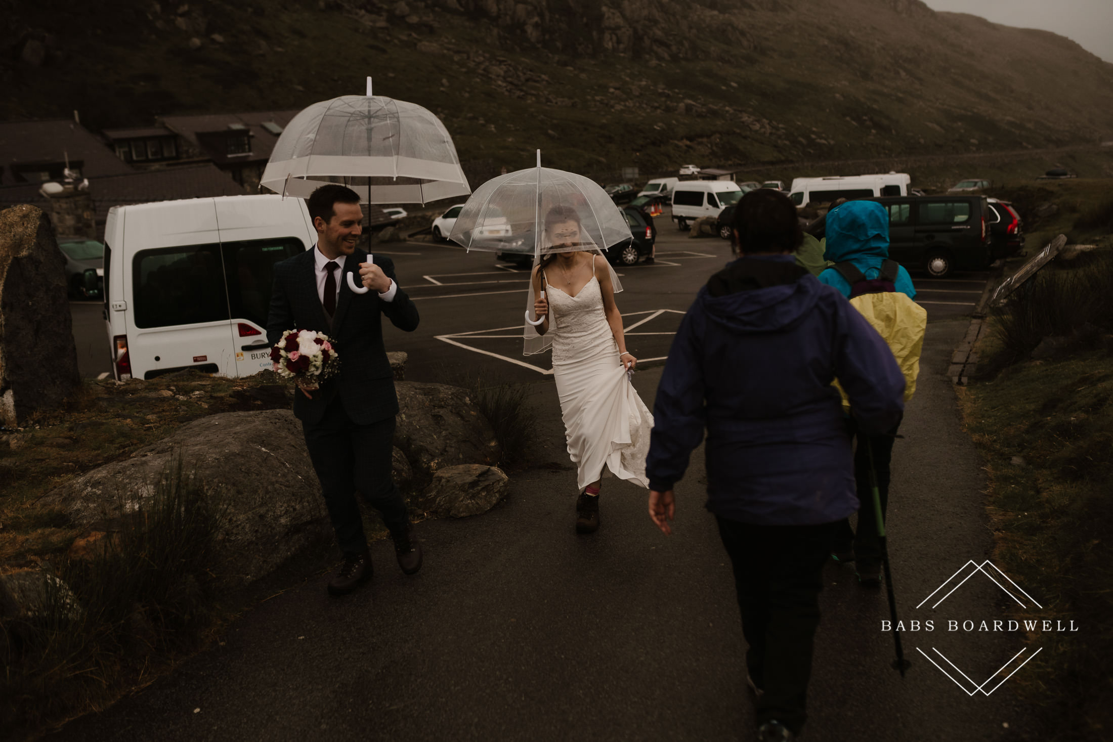 bride and groom walking towards a group of walkers holding transparent umbrellas at Pen Y Pass by Snowdonia Wedding Photographer