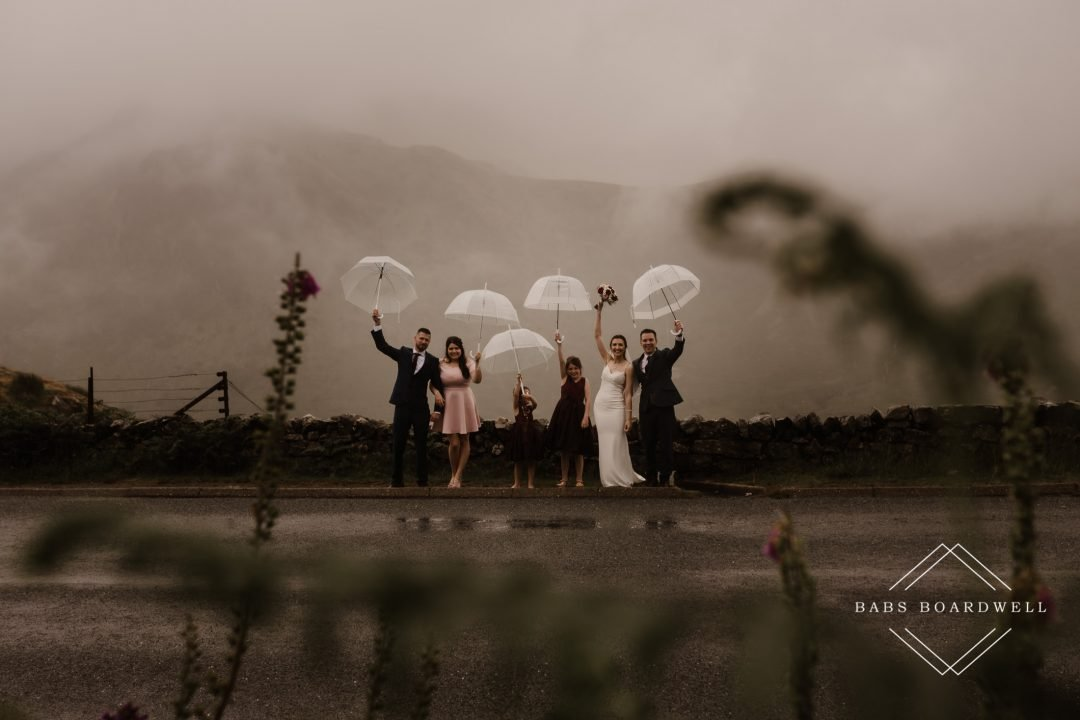 group portrait in the rain with bridal party holding transparent umbrellas above their heads by Snowdonia Wedding Photographer