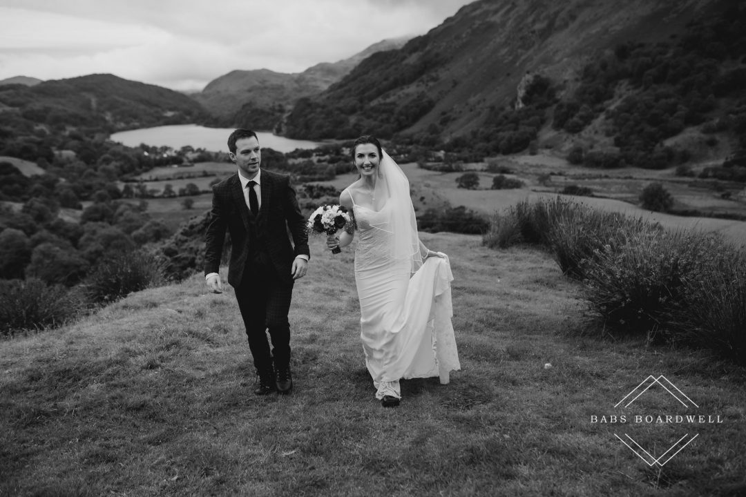 black and white image of bride and groom walking next to each other on their wedding day above Llyn Gwynant by Snowdonia Wedding Photographer