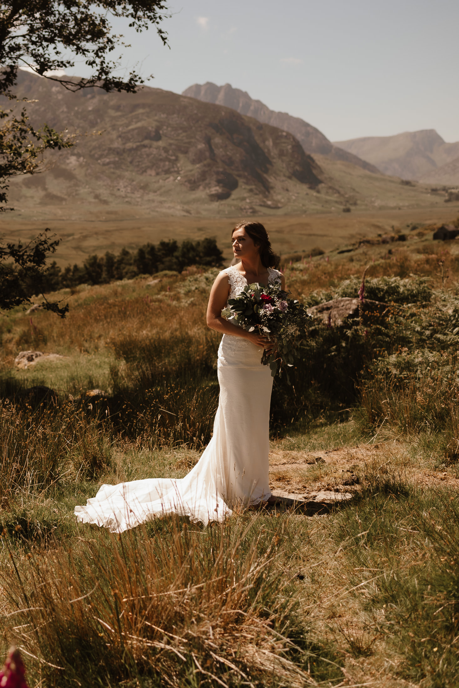 bride holding her bouquet with Tryfan in the background by Snowdonia Wedding & Elopement Photographer Babs Boardwell