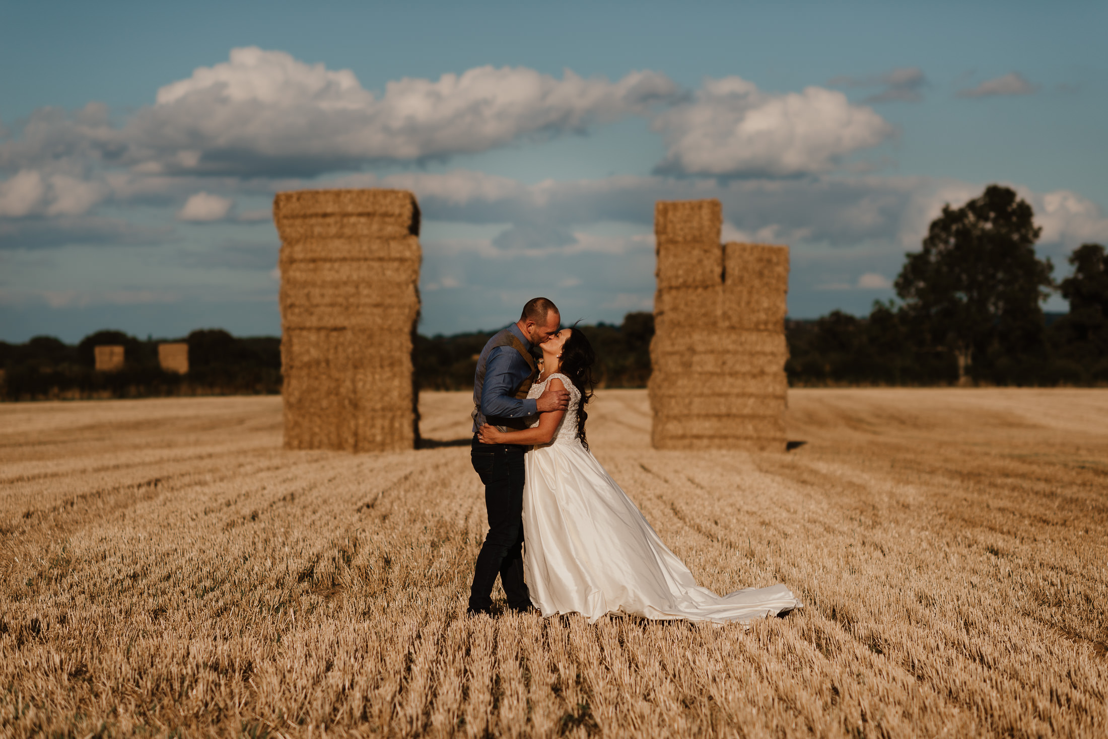 bride and groom kissing between 2 straw stacks on a field against a blue sky by North Wales Wedding Photographer