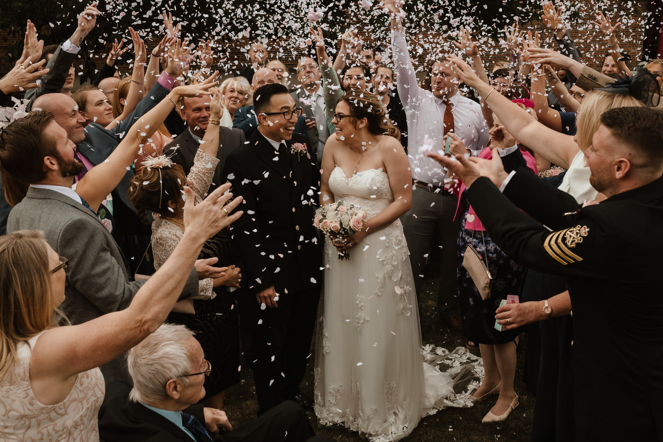 bride and military groom in the centre with family and friends throwing confetti by North Wales Wedding Photographer