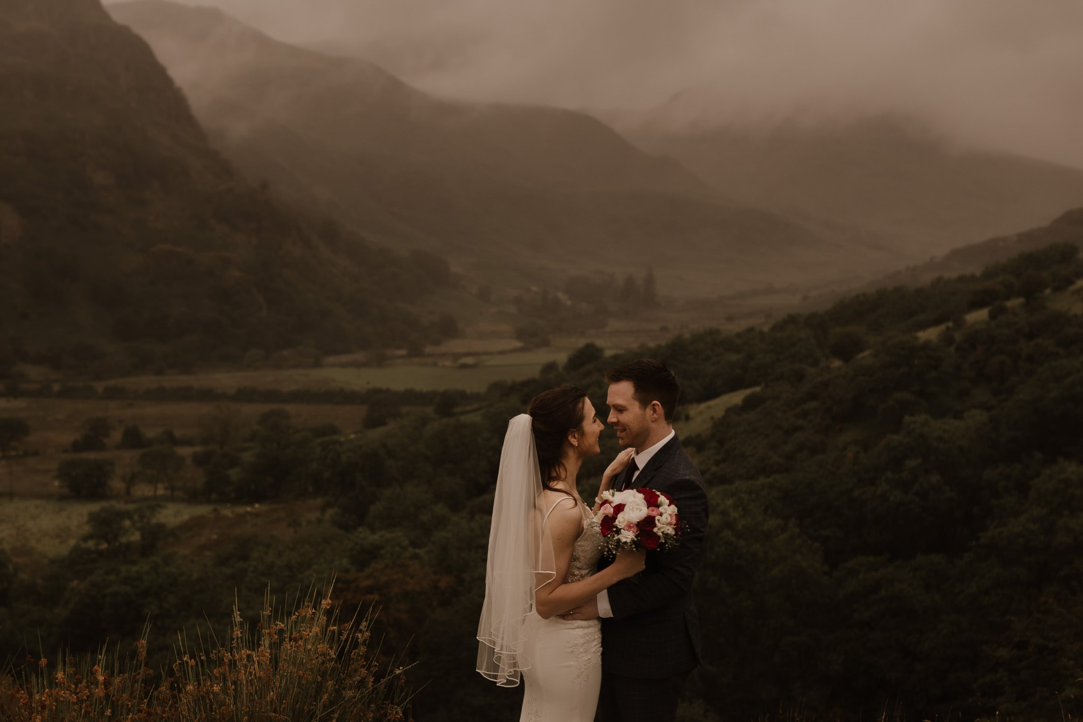 bride and groom hugging against the backdrop of the Snowdon range by North Wales Wedding & Elopement Photographer