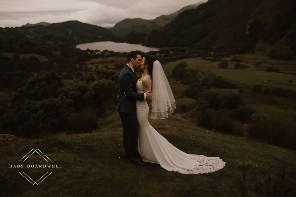 bride and groom hugging and kissing in their wedding outfits with Llyn Gwynant and mountains in the background