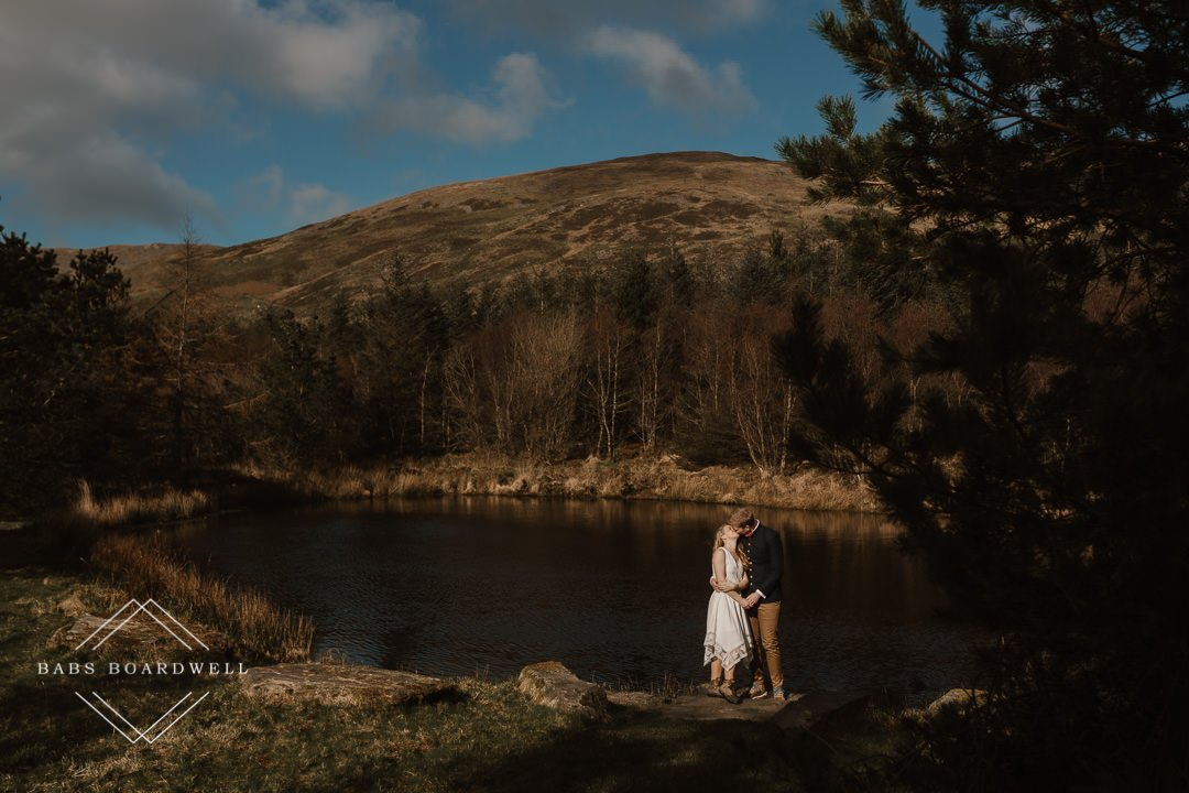 bride and groom standing on a jetty kissing with a lake and mountain and blue sky behind them by Snowdonia Wedding Photographer