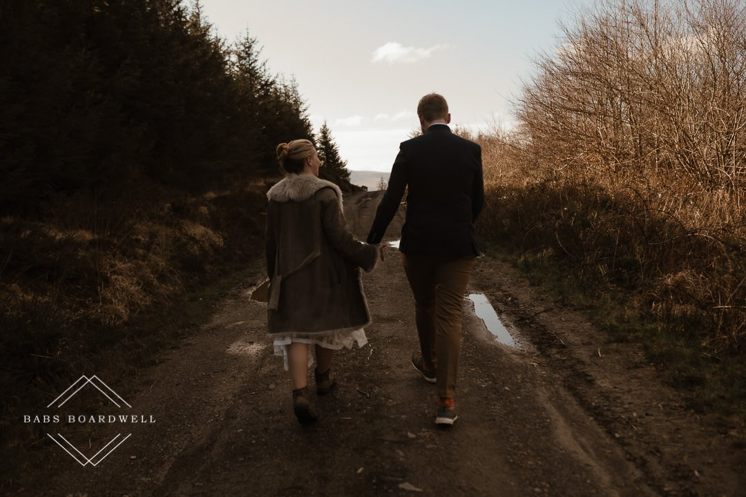 bride and groom walking hand in hand on their elopement day by Snowdonia Wedding Photographer