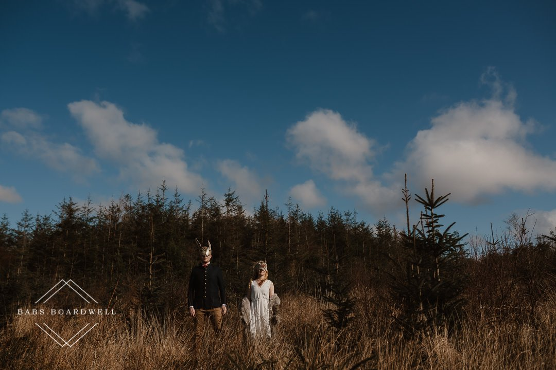 bride and groom wearing animal masks with a forest and blue sky in the background by Snowdonia Wedding Photographer