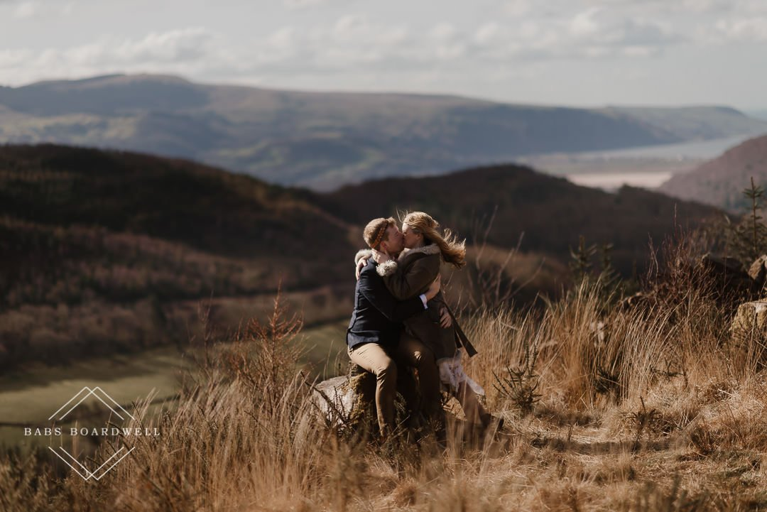 groom sitting on a rock kissing his bride against the backdrop of Barmouth by Snowdonia Wedding Photographer