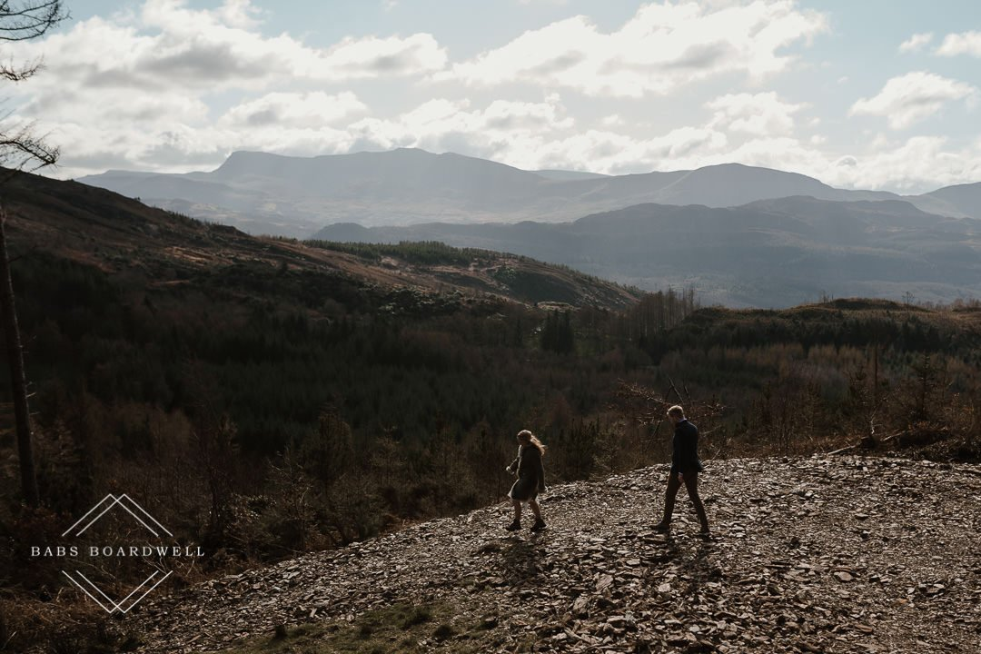bride and groom walking on a track with a mountain range in the background by Snowdonia Wedding Photographer