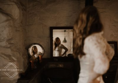 bride on her elopement day looking at her herself in the mirrors wearing her wearing dress by Snowdonia Wedding Photographer