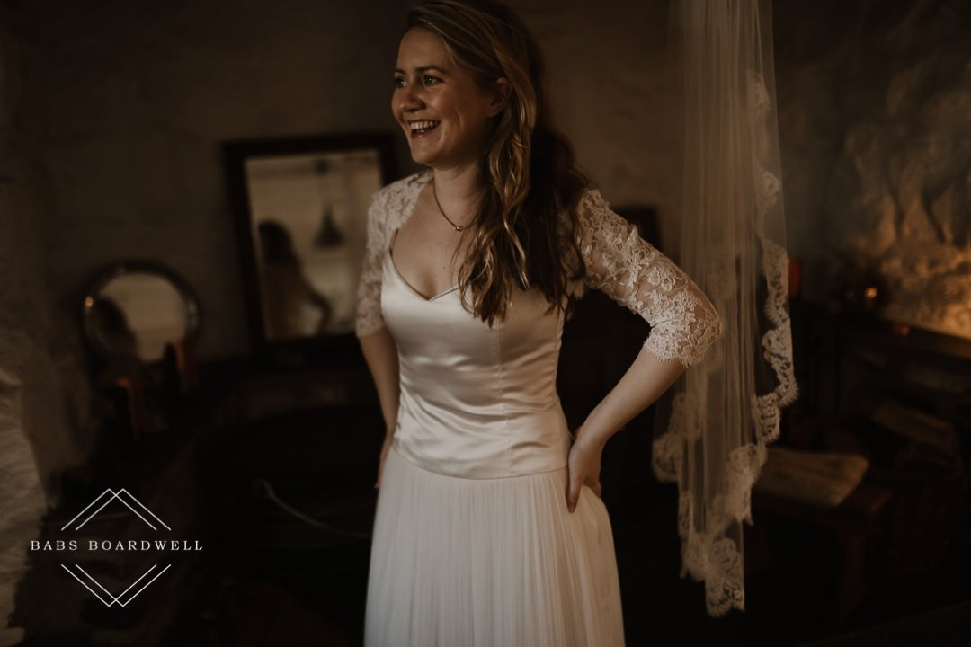 bride smiling on her elopement day putting her dress on by Snowdonia Wedding Photographer