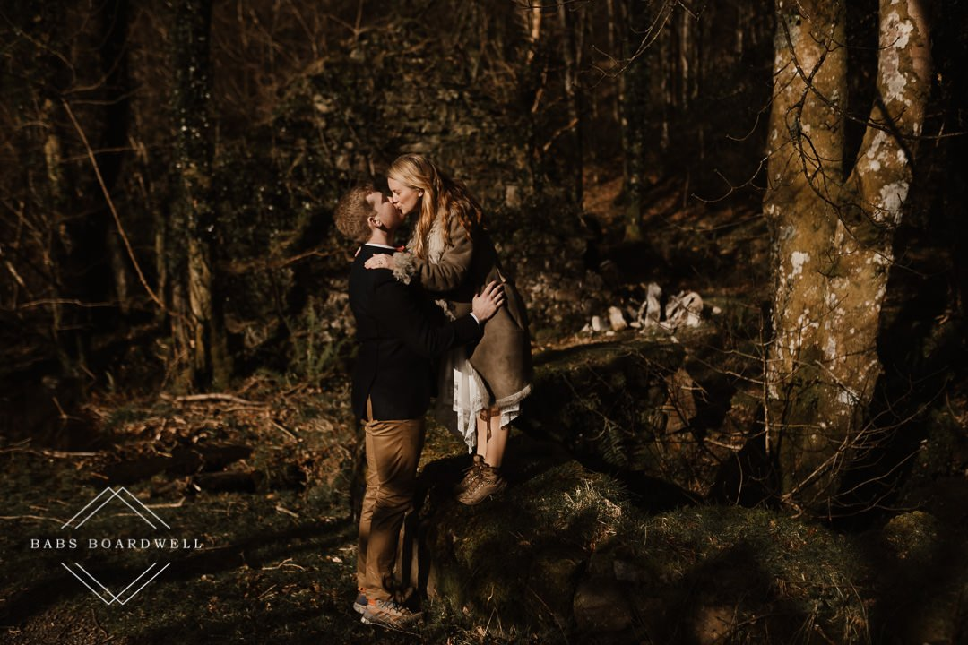 couple hugging in the woods with the woman standing on a little stone wall