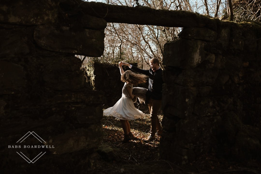 couple twirling in a ruin's archway on their elopement day by Snowdonia Elopement Photographer