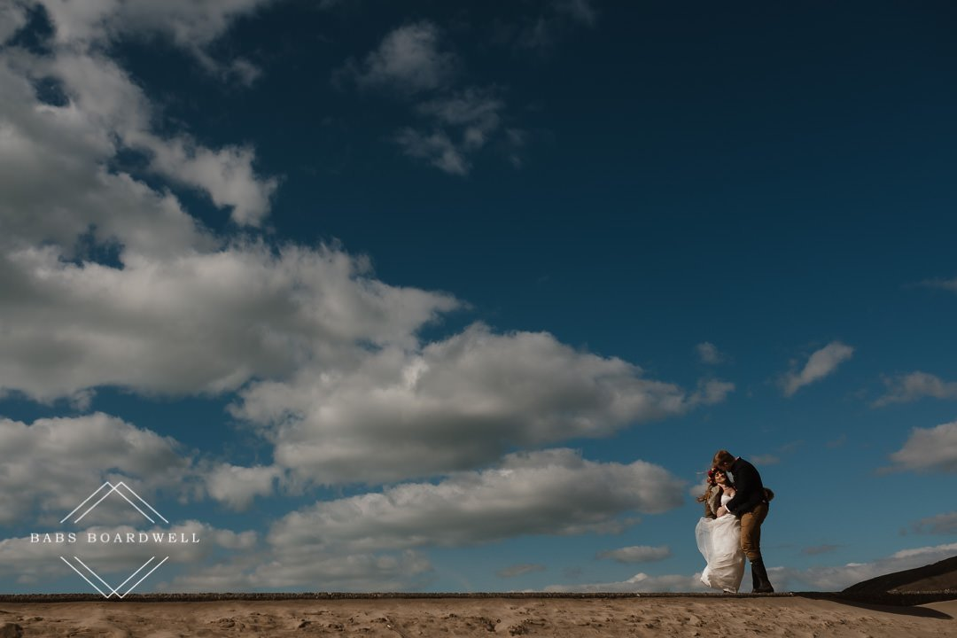 bride and groom at Barmouth Beach on their elopement day kissing with a blue sky in the background by Snowdonia Wedding Photographer