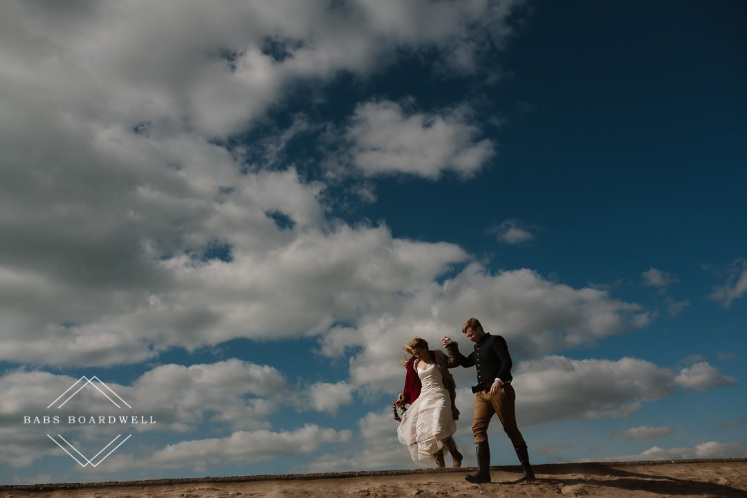 bride and groom walking at Barmouth Beach on their elopement day by Snowdonia Wedding Photographer