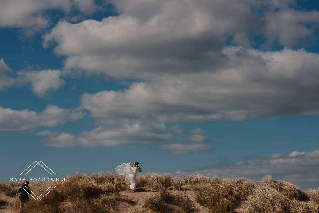 bride and groom walking around the dunes on their elopement day by Snowdonia Wedding Photographer