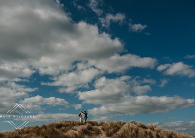 bride and groom on a sand dune at Barmouth Beach twirling on their elopement day by Snowdonia Wedding Photographer