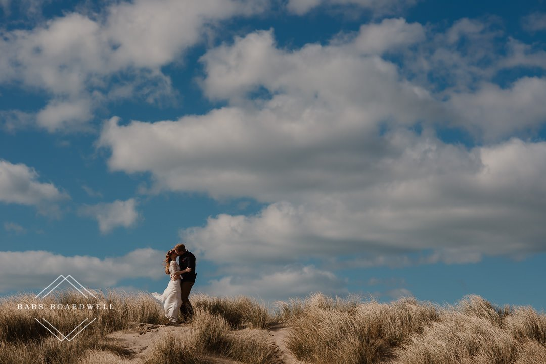 bride and groom kissing on a dune at Barmouth Beach on their Elopement Day by Snowdonia Wedding Photographer