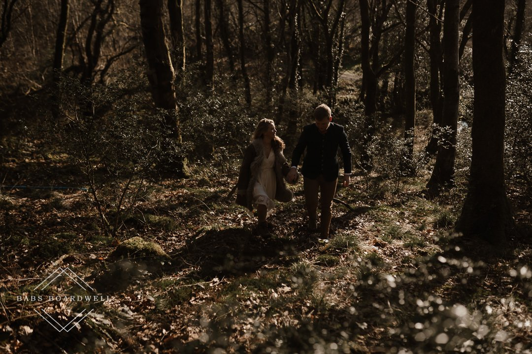 couple walking uphill in a sunlit forest on their elopement day by Snowdonia Wedding Photographer