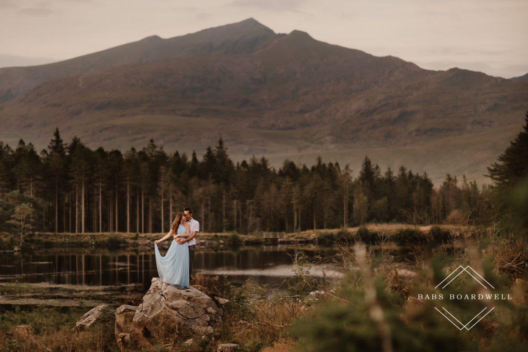 groom and bride wearing a blue wedding dress on a tree stump with Snowdon in the background by North Wales Wedding & Elopement Photographer