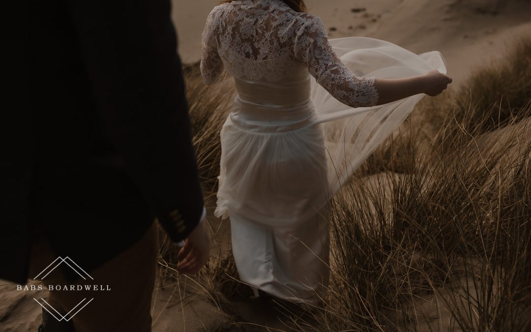 close up of bride's dress details on Barmouth Beach by Snowdonia Wedding Photographer