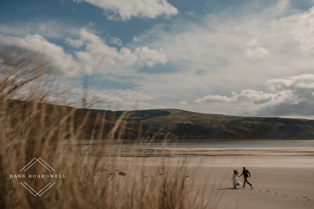 bride and groom running on Barmouth Beach on a sunny day with blue sky and mountains in the background by Snowdonia Wedding Photographer