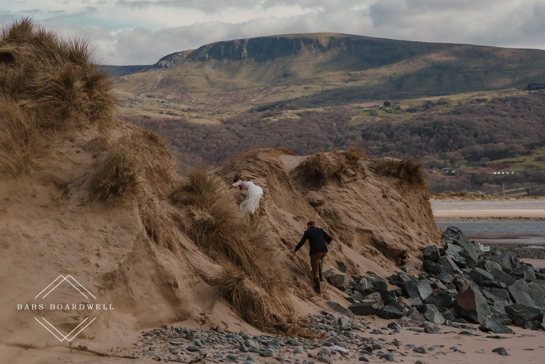 bride and groom climbing up a sand dune on their elopement day on Barmouth Beach by Snowdonia Wedding Photographer
