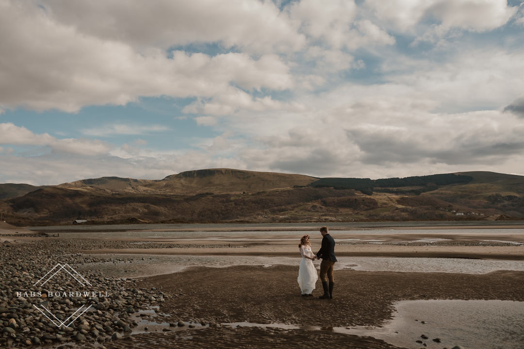 bride and groom standing on Barmouth Beach with mountains in the background
