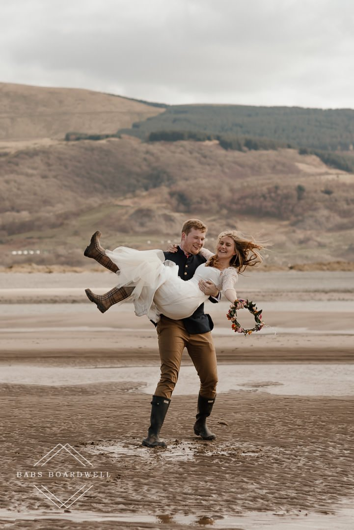 portrait of bride and groom twirling on Barmouth Beach on their elopement day by Snowdonia Wedding Photographer