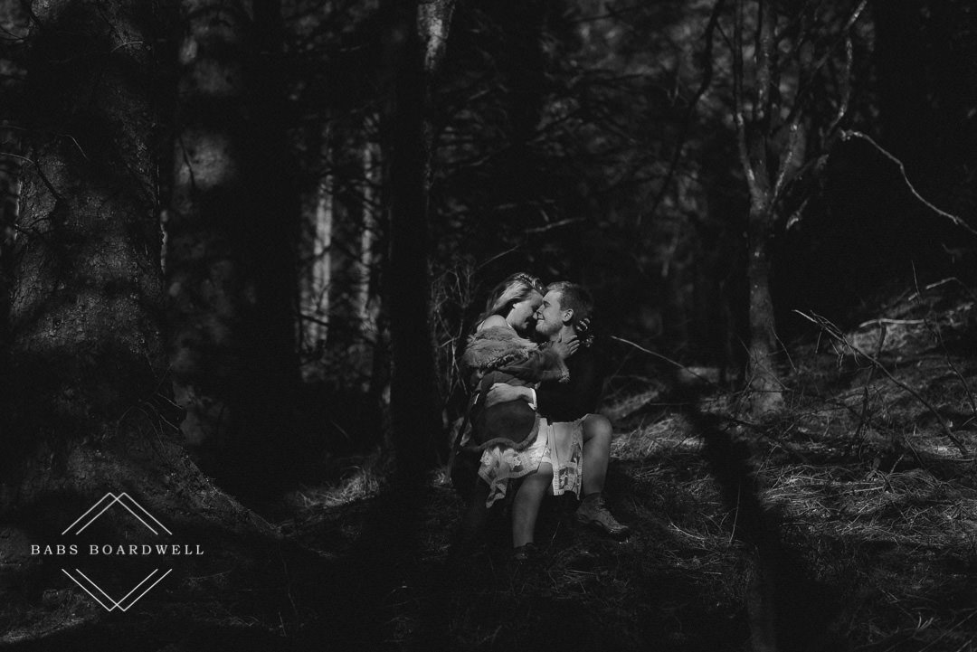 black and white image of bride and groom sitting on a tree stump in the middle of the forest by Snowdonia wedding Photographer