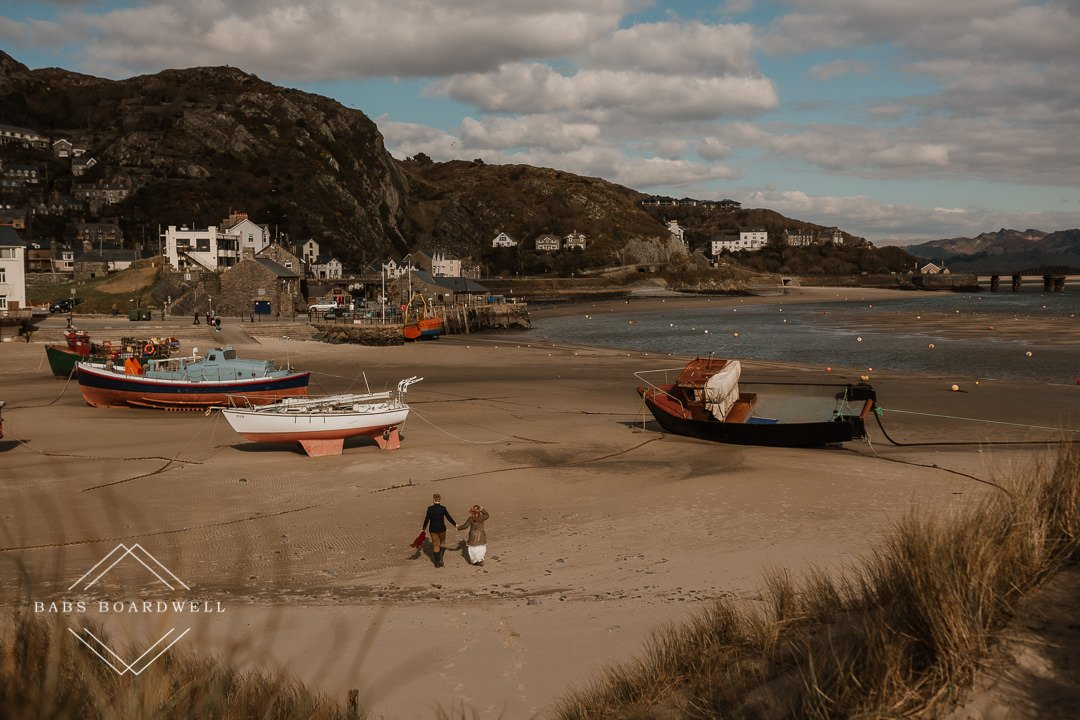 bride and groom walking on Barmouth Beach with boats in the background