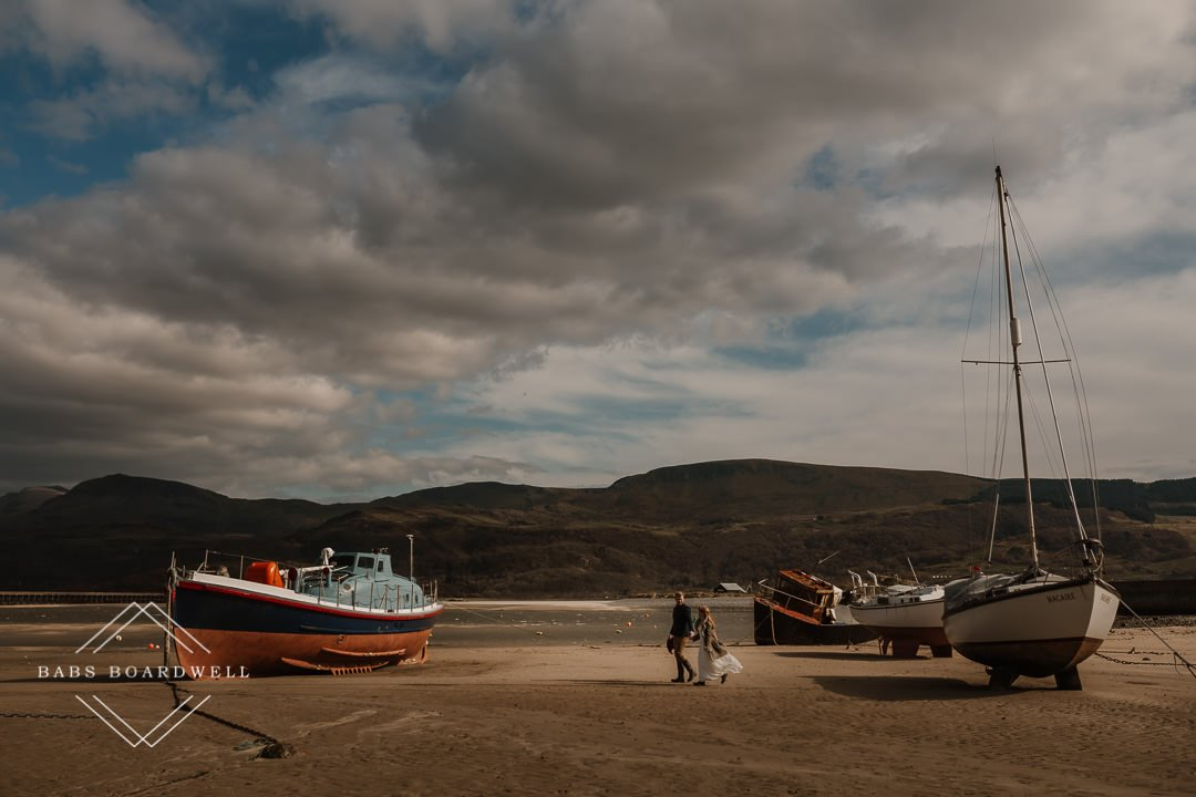 bride and groom walking amongst boats on Barmouth Beach by the harbour