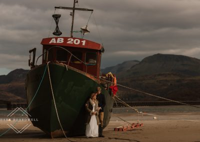 bride and groom standing by a boat in Barmouth Harbour