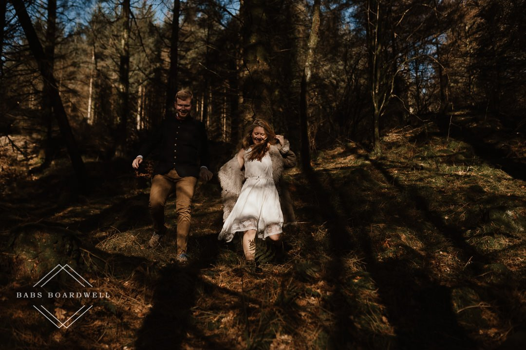 bride and groom running downhill in a forest by Snowdonia Wedding Photographer