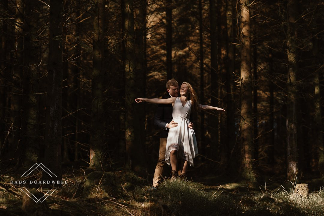 bride and groom in the forest with the bride standing on a tree stump and her arms stretched out on either side by Snowdonia Wedding Photographer