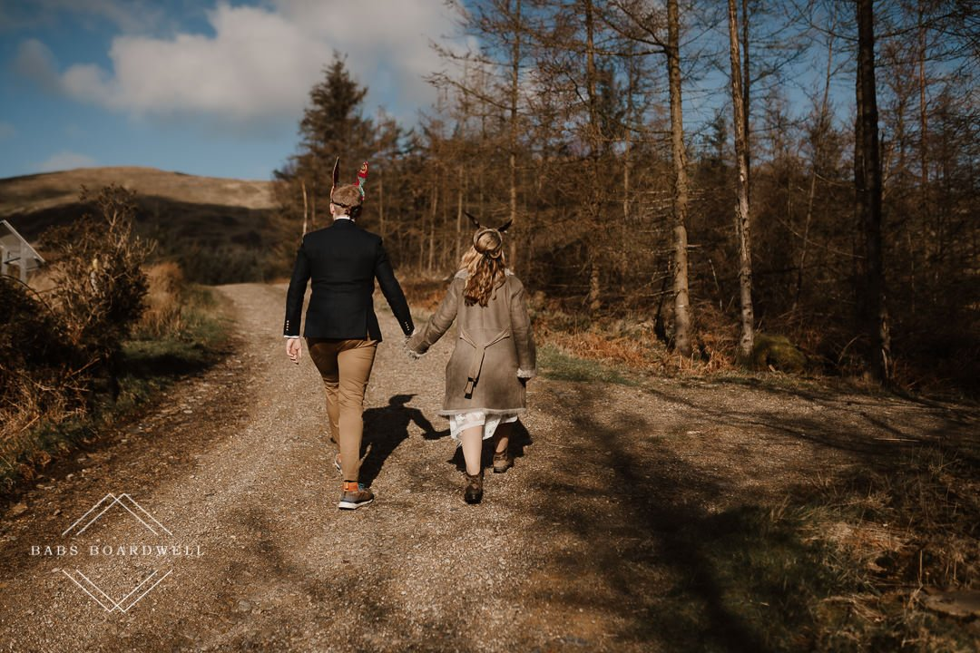 bride and groom walking on a forest track on their elopement day Snowdonia Wedding Photographer
