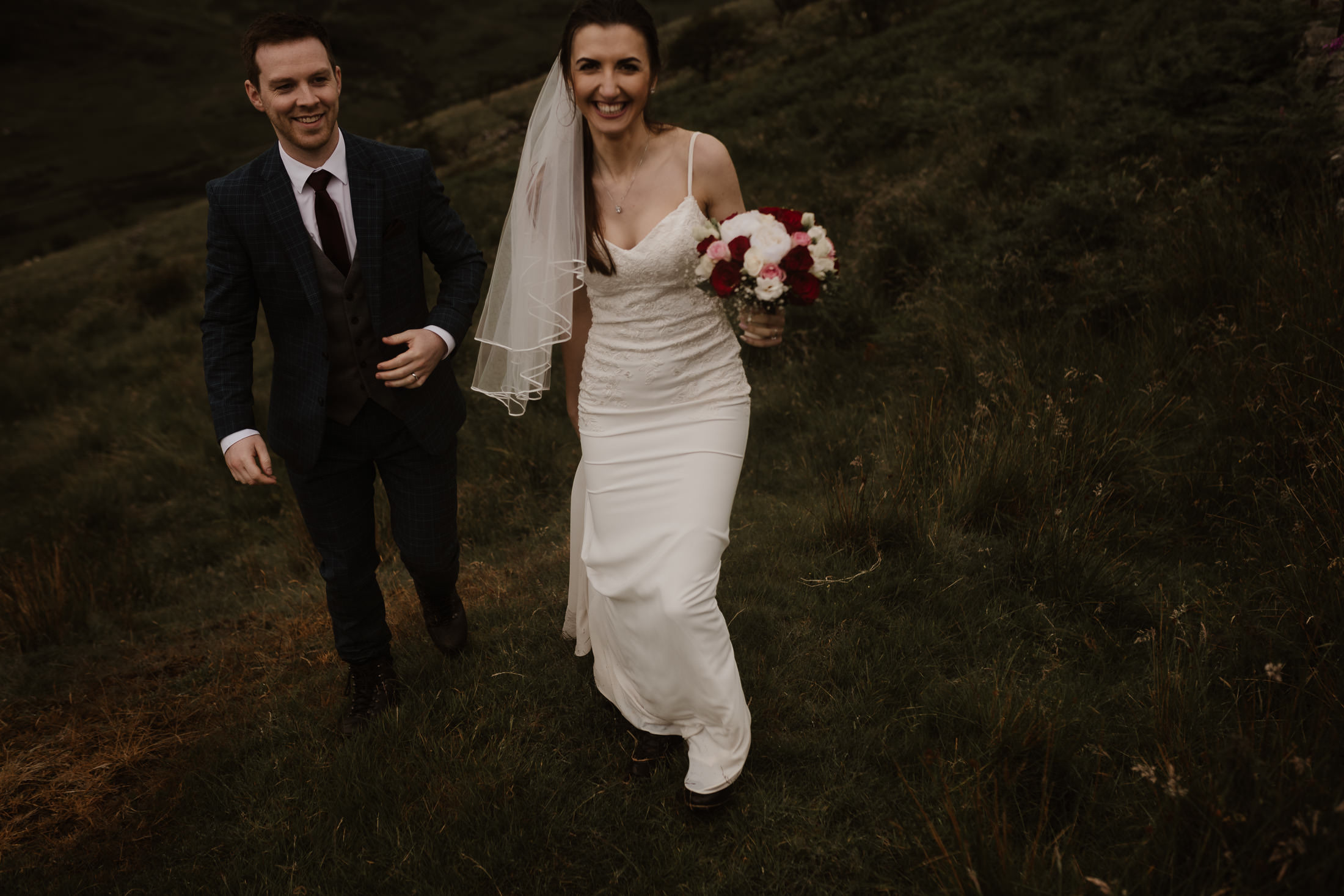 bride and groom with beaming smiles on their faces walking towards Snowdonia Wedding Photographer