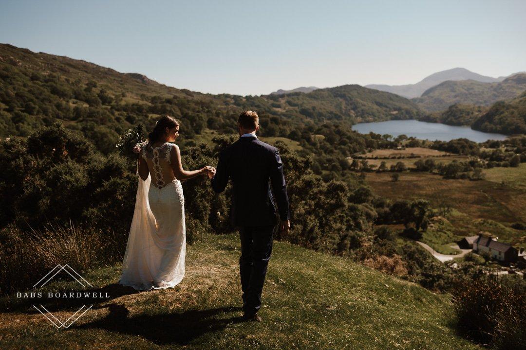 bride and groom walking towards Llyn Gwynant wearing their wedding outfits by Snowdonia Wedding Photographer