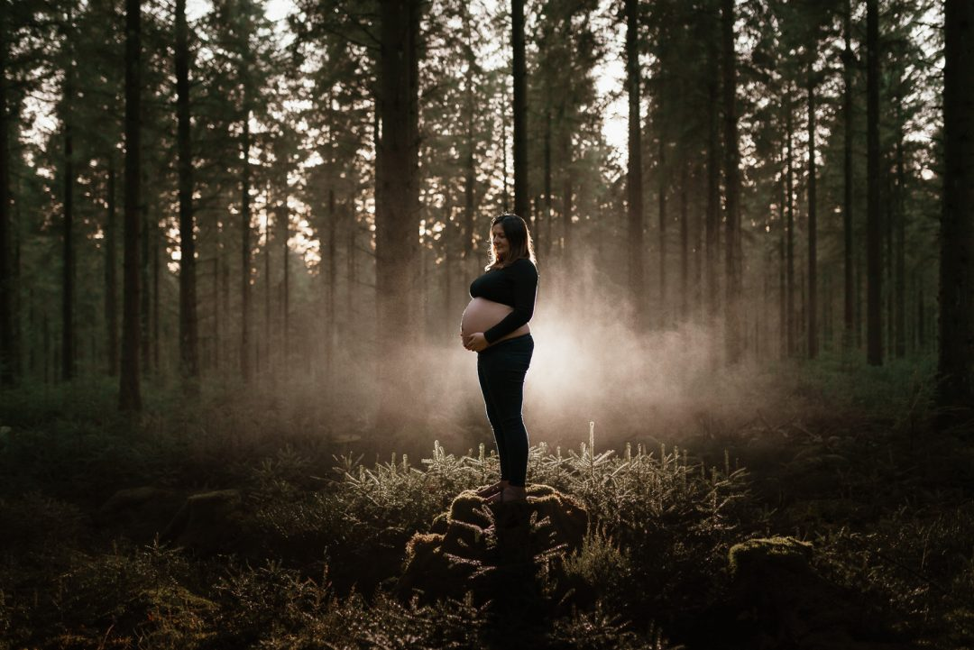 Pregnant woman standing on a tree stump in a forest with her bump being lit from behind by North Wales Maternity Photographer