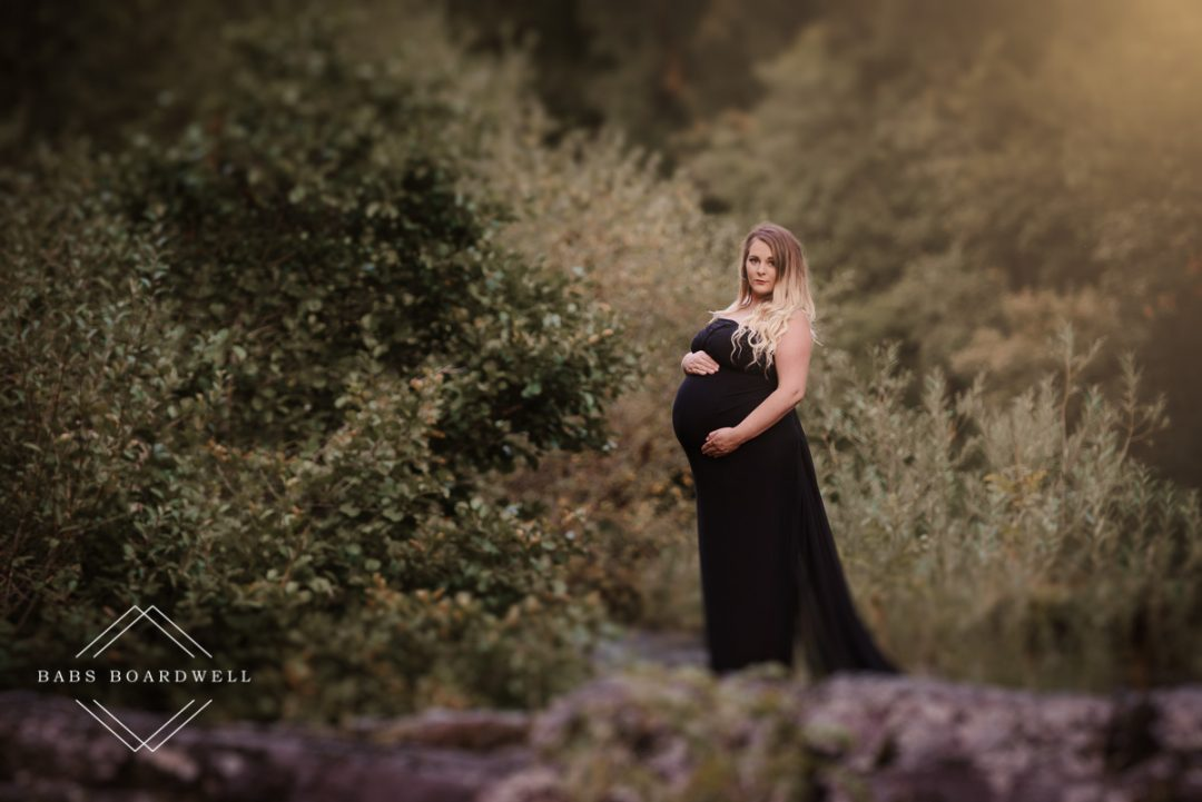pregnant woman in a black dress during her maternity session